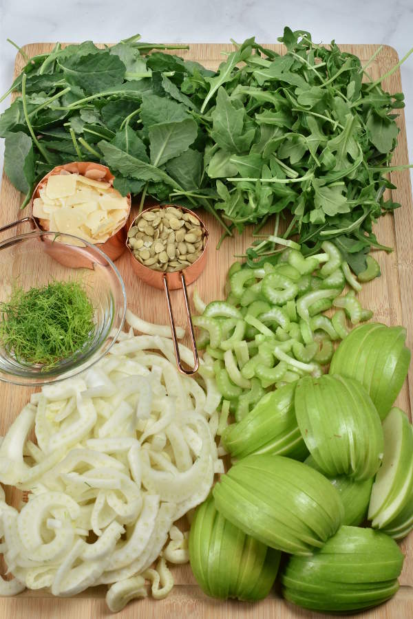 Ingredients for Apple Fennel Salad sliced and prepared on a cutting board.