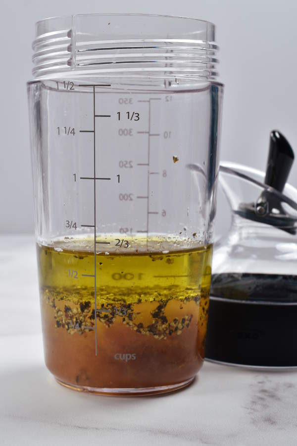Unmixed apple vinaigrette dressing ingredients in a shaker bottle.