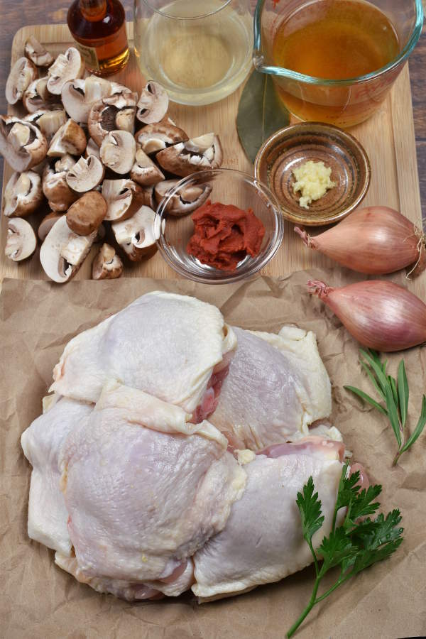 Ingredients for chicken chasseur on a cutting board.