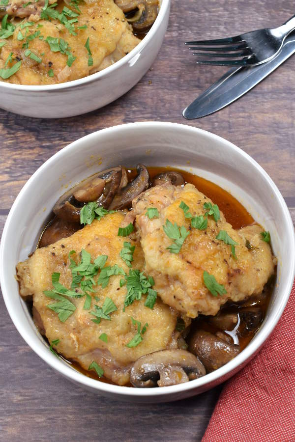 Two chicken thighs with mushrooms and sauce garnished with parsley.