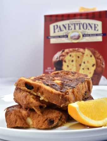 Three slices of panettone French toast garnished with an orange slice with the panettone box in the background.