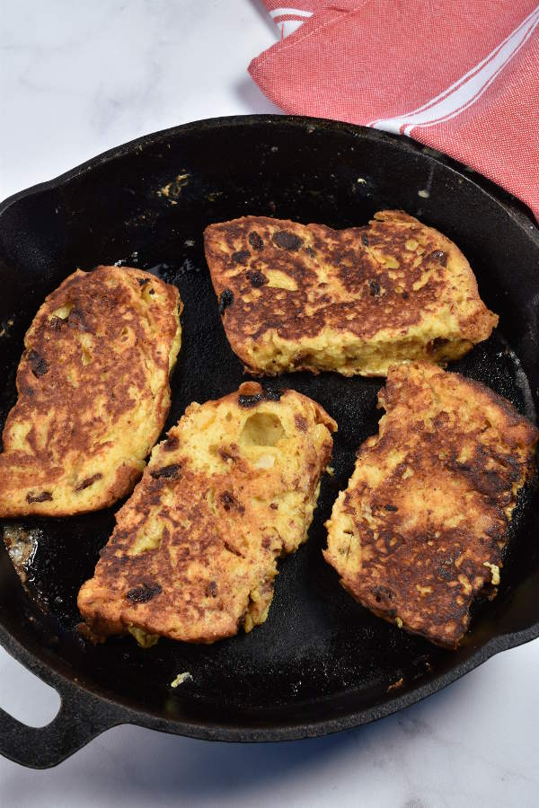 Four slices of panettone French toast in a cast iron skillet.