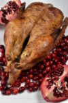 Whole roast duck arranged with cranberries and pomegranates on a serving platter.